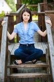 La mujer joven se sienta en escala de madera Fotos de archivo libres de regalías