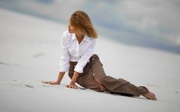 La mujer joven se sienta en la arena en desierto y mira pensativamente a un lado Fotografía de archivo libre de regalías
