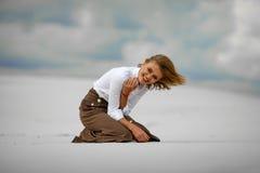 La mujer joven se sienta en la arena en desierto y risas alegres Imagen de archivo