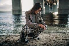 La mujer joven se sienta en la orilla del río debajo del puente fotos de archivo libres de regalías