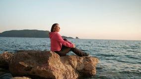 La mujer joven se sienta en roca por el agua al aire libre almacen de video