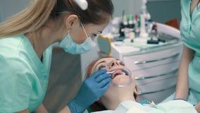 La mujer joven se sienta en silla en la recepción en el dentista metrajes