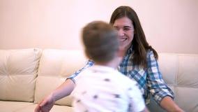 La mujer joven se sienta en Sofa And Turns On TV almacen de metraje de vídeo