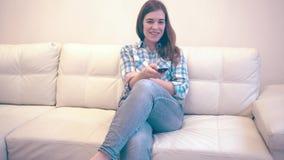 La mujer joven se sienta en Sofa And Turns On TV almacen de video