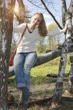 La mujer joven se sienta en un tronco del caído abajo de abedul Fotos de archivo libres de regalías