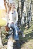 La mujer joven se sienta en un tronco del caído abajo de abedul Foto de archivo