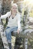 La mujer joven se sienta en un tronco del caído abajo de abedul Fotografía de archivo libre de regalías