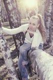 La mujer joven se sienta en un tronco del caído abajo del abedul, entonando Fotografía de archivo