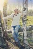 La mujer joven se sienta en un tronco del caído abajo del abedul, entonando Fotos de archivo