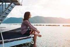 La mujer joven se sienta solamente en el puente tiene río, montaña, cielo es CCB Imagenes de archivo