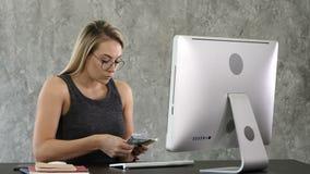 La mujer joven se sienta y contando el dinero en la oficina almacen de video