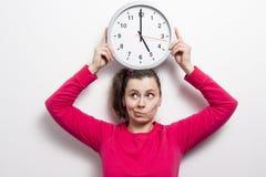 La mujer joven se sostiene alrededor del reloj sobre su cabeza en el fondo blanco Imagen de archivo libre de regalías