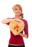 La mujer joven se sostiene en rectángulo de regalo del oro de las manos como corazón Imagen de archivo