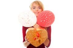 La mujer joven se sostiene en rectángulo y globos de regalo de las manos Imagen de archivo libre de regalías