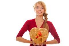 La mujer joven se sostiene en rectángulo de regalo de las manos como corazón Fotografía de archivo