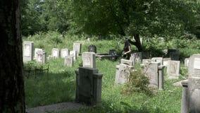La mujer joven se vistió en ropa fúnebre que caminaba en cementerio entre sepulcros almacen de video