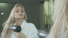 La mujer joven seca el pelo mojado delante del espejo con el hairdryer almacen de metraje de vídeo