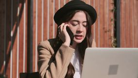 La mujer joven seria está discutiendo por el teléfono móvil y está utilizando el ordenador portátil en la calle metrajes