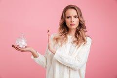 La mujer joven seria que sostiene la melcocha hace gesto de la parada foto de archivo libre de regalías