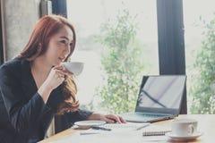 La mujer joven sienta el trabajo en una cafetería, empleados está trabajando fuera de la compañía, estudiantes está buscando para imagen de archivo libre de regalías