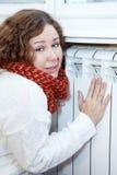 La mujer joven siente frío el sentarse cerca de estafa de la calefacción Fotos de archivo