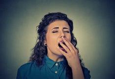 La mujer joven soñolienta con los ojos de bostezo de la boca abierta de par en par se cerró foto de archivo libre de regalías