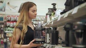 La mujer joven sola está comparando el modelo de las máquinas del café en una tienda del hardware almacen de video