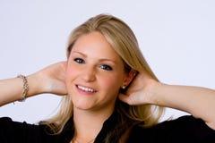 La mujer joven sonríe en la cámara. Imagen de archivo