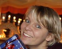 La mujer joven sonríe sobre presente Foto de archivo