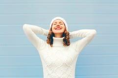 La mujer joven sonriente bonita feliz disfruta de un buen día que lleva el sombrero y el suéter hechos punto sobre azul Imagen de archivo