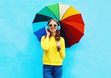 La mujer joven sonriente bonita feliz escucha la música en auriculares con el paraguas colorido en día del otoño sobre fondo azul Imagen de archivo libre de regalías