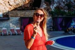 La mujer joven sonriente come el helado de chocolate en verano imagen de archivo libre de regalías