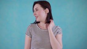 La mujer joven sonriente con el deterioro de oído oye con el audífono en oído en fondo azul almacen de metraje de vídeo