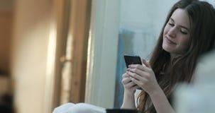 La mujer joven sonriente con el pelo oscuro largo lee algo en su smartphone que se sienta en el piso en un cuarto almacen de video