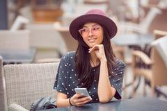 La mujer joven sonriente con el teléfono elegante en café hace compras foto de archivo libre de regalías