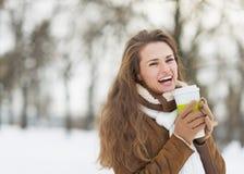 La mujer joven sonriente con la taza de bebida caliente en invierno parquea Fotos de archivo libres de regalías