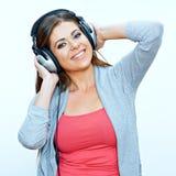 La mujer joven sonriente con los auriculares escucha música Imagen de archivo