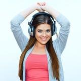 La mujer joven sonriente con los auriculares escucha música Fotos de archivo