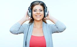La mujer joven sonriente con los auriculares escucha música Foto de archivo libre de regalías