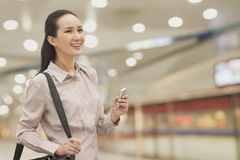 La mujer joven sonriente con una cola de caballo que sostiene el teléfono móvil, dentro, se centra en primero plano Fotos de archivo libres de regalías