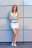 La mujer joven sonriente cruzó los brazos por la pared moderna Foto de archivo