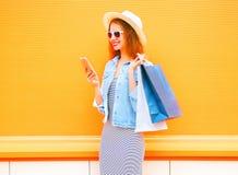 La mujer joven sonriente de la moda está utilizando el smartphone en la ciudad Imágenes de archivo libres de regalías