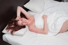 La mujer joven sonriente despierta en malo Fotos de archivo libres de regalías