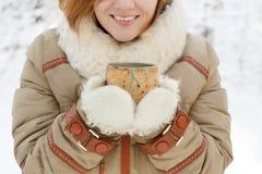 La mujer joven sonriente en abrigo de invierno y las manoplas mullidas blancas se sostienen Fotos de archivo libres de regalías