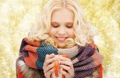 La mujer joven sonriente en invierno viste con la taza Imagenes de archivo