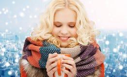 La mujer joven sonriente en invierno viste con la taza Imagen de archivo