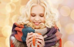 La mujer joven sonriente en invierno viste con la taza Fotografía de archivo libre de regalías