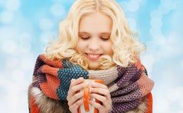 La mujer joven sonriente en invierno viste con la taza Foto de archivo libre de regalías