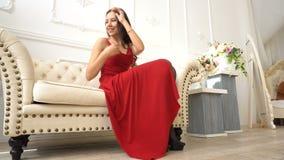 La mujer joven sonriente en medias y el vestido rojo se sientan en el sofá almacen de video