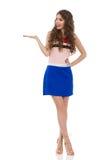 La mujer joven sonriente en Mini Dress And High Heels está presentando imagen de archivo libre de regalías